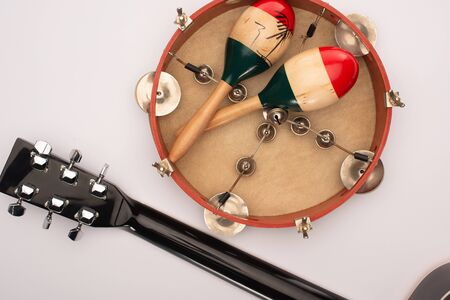 Top view of acoustic guitar near wooden maracas on tambourine on white background 写真素材
