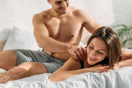 selective focus of sexy shirtless man making shoulders erotic massage to pretty girlfriend lying and smiling with closed eyes