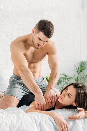 handsome shirtless man making arm erotic massage to sexy girlfriend Banque d'images