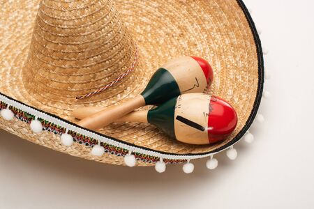 Close up view of wooden maracas on sombrero on white background