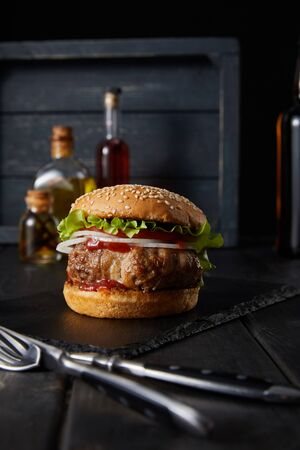 selective focus of burger on dark chopping board near fork, knife, oil and vinegar bottles isolated on black
