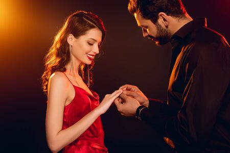 Side view of man putting ring on finger of smiling girlfriend in red dress on black background with lighting