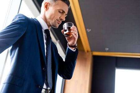 low angle view of handsome businessman in suit drinking cognac Reklamní fotografie