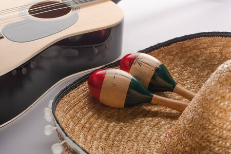 Close up view of wooden maracas on sombrero and acoustic guitar on white background 写真素材
