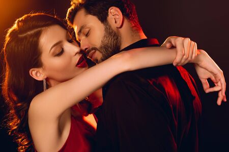Side view of handsome man kissing elegant girlfriend with red lips on black background with lighting