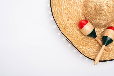 Top view of sombrero and maracas on white background