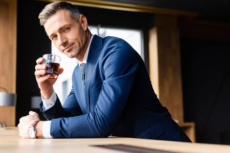 businessman in suit holding glass and looking at camera Reklamní fotografie