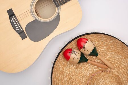 Top view of acoustic guitar with wooden maracas on sombrero on white background 写真素材