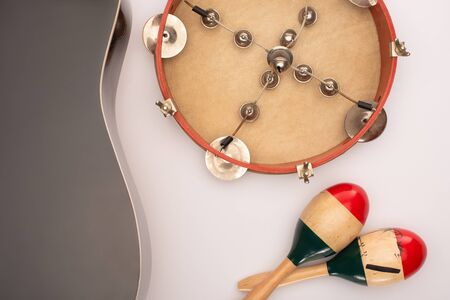 Top view of acoustic guitar near wooden maracas and tambourine on white 写真素材