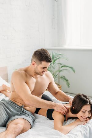 sexy shirtless man making shoulders erotic massage to girlfriend lying and smiling with closed eyes