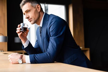 handsome businessman in suit holding glass and looking away