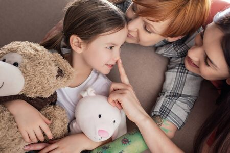Smiling same sex parents kissing and touching nose of daughter with soft toys on couch Stock Photo