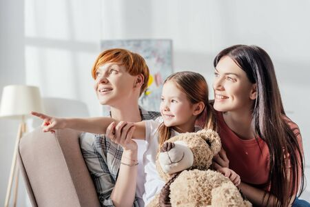 Smiling kid with teddy bear pointing with finger near mothers while sitting on couch in living room