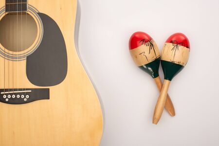 Top view of acoustic guitar near wooden maracas on white