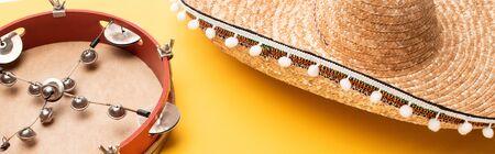 Tambourine and sombrero on yellow background, panoramic shot