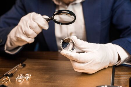 Cropped view of jewelry appraiser holding gemstone and magnifying glass near jewelry rings on board on table isolated on black