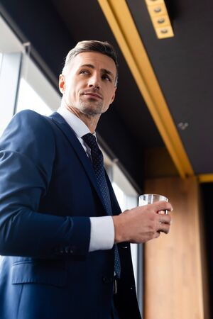 low angle view of handsome businessman in suit holding glass Reklamní fotografie