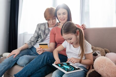 KYIV, UKRAINE - FEBRUARY 10, 2020: Child using digital tablet with youtube app on screen near mothers with credit card on couch Stockfoto