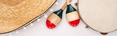 Top view of wooden maracas with tambourine and sombrero on white background, panoramic shot