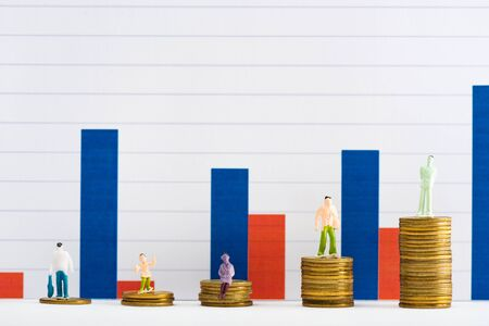 People figures on coins on white surface with graphs at background, concept of financial equality Stock Photo