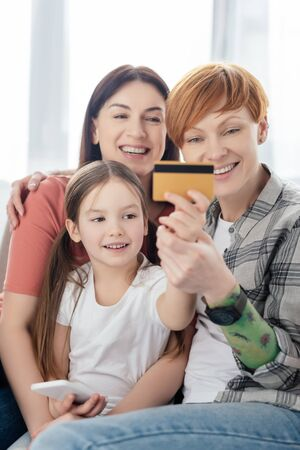 Selective focus of smiling kid with smartphone holding credit card near same parents on sofa