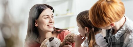 Selective focus of smiling mother holding teddy bear near daughter and parent in living room, panoramic shot