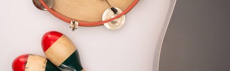 Top view of acoustic guitar near wooden maracas and tambourine on white background, panoramic shot 写真素材