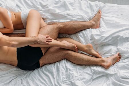cropped view of sexy couple in underwear hugging on white bedding, top view Stockfoto