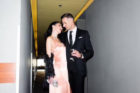handsome boyfriend with glass kissing smiling girlfriend in hotel Reklamní fotografie