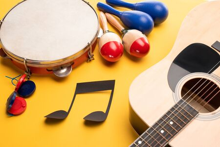 Musical instruments and paper cut music note on yellow background