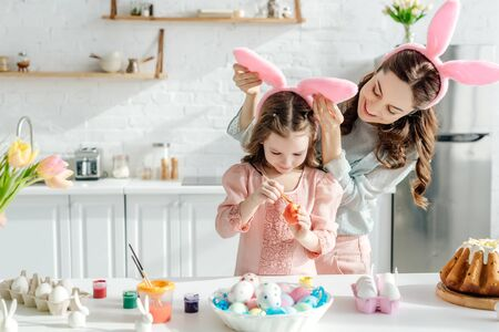 selective focus of happy mother touching bunny ears on daughter painting chicken egg near easter bread
