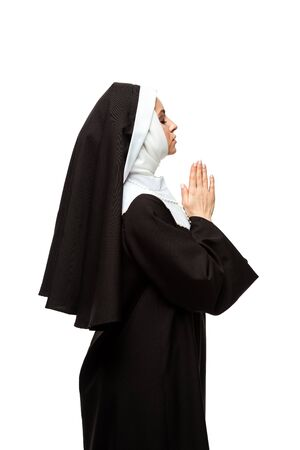 beautiful nun praying with closed eyes and hands together isolated on white
