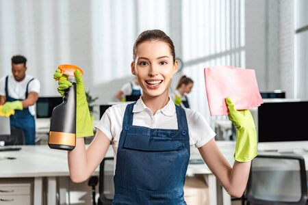 happy cleaner in overalls holding spray bottle and rag while looking at camera