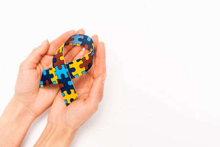 Cropped view of awareness ribbon in female hands on white, autism concept