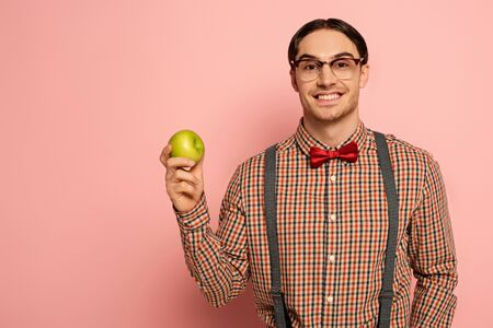 cheerful male nerd in eyeglasses holding apple on pink