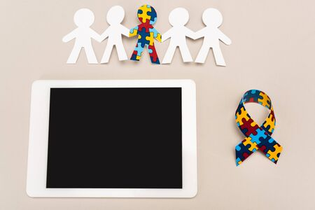 Top view of awareness ribbon, digital tablet and special kid with autism among another on white background Stock Photo