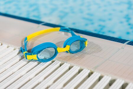 goggles near swimming pool with blue water