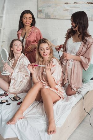 Multicultural friends doing hairstyles on bed at bachelorette party