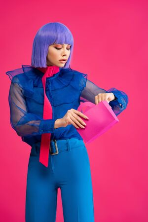beautiful stylish girl in purple wig holding little shopping bag, isolated on pink