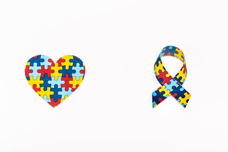 Top view of puzzle heart and awareness ribbon isolated on white, autism concept