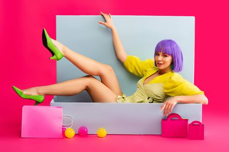 beautiful emotional girl in purple wig as doll lying in blue box with shopping bags and balls, on pink 스톡 콘텐츠
