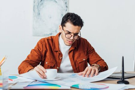 Ux designer drinking coffee while working with app templates and color circles at table