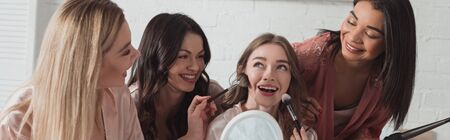Multicultural women with putting makeup with cosmetic brushes on bride, smiling together in room, panoramic shot