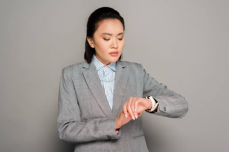 young businesswoman in suit looking at wristwatch on grey background