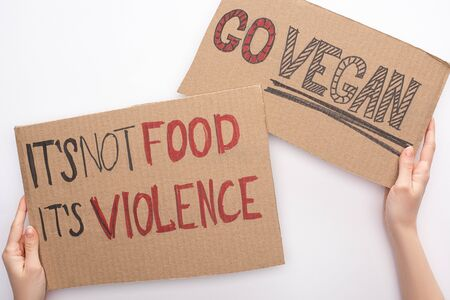 partial view of woman holding cardboard signs with go vegan and its not food its violence inscriptions on white background Standard-Bild - 142843386