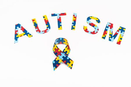 High angle view of Autism puzzle lettering and awareness ribbon isolated on white