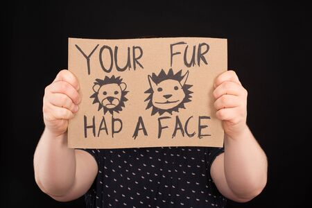 man with obscure face holding sign with your fur had a face inscription isolated on black