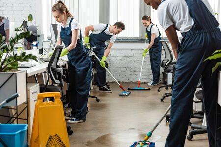 multicultural team of young cleaners washing floor with mops in office
