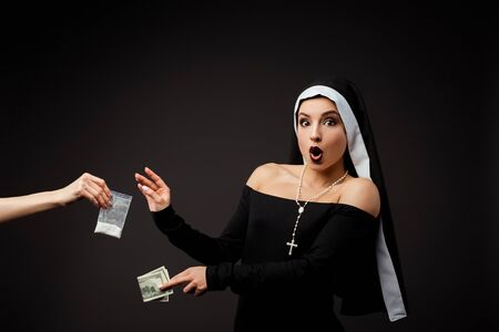shocked nun with money buying plastic bag of cocaine isolated on grey