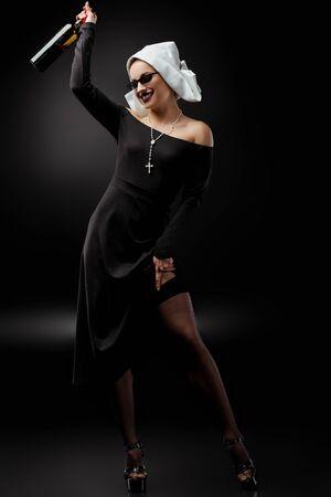 happy nun in sunglasses holding bottle of wine on grey